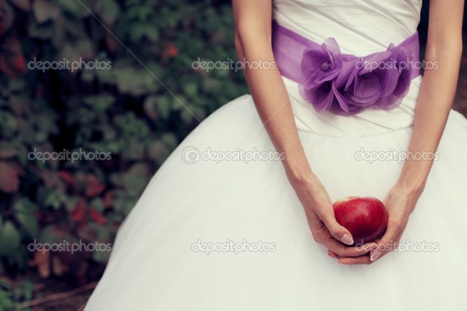 Bride's hands holding red apple - symbol of love - over white va