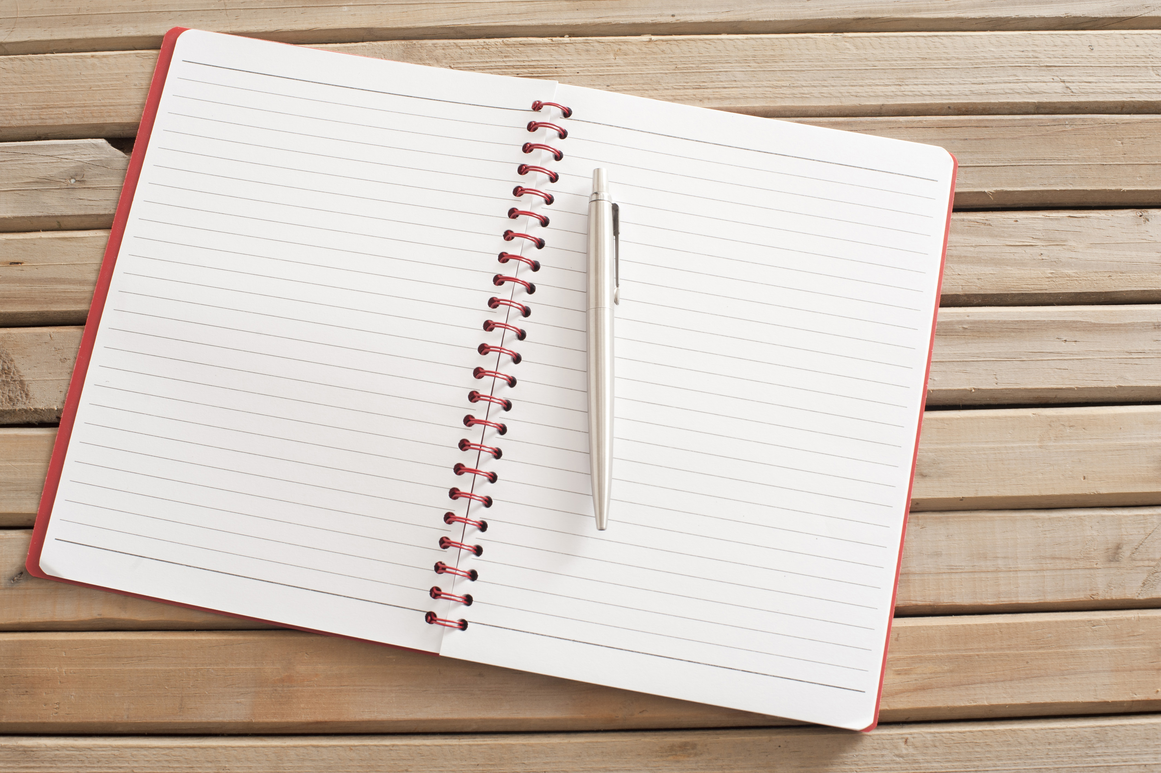 Open Blank Notebook with Pen on Wooden Table